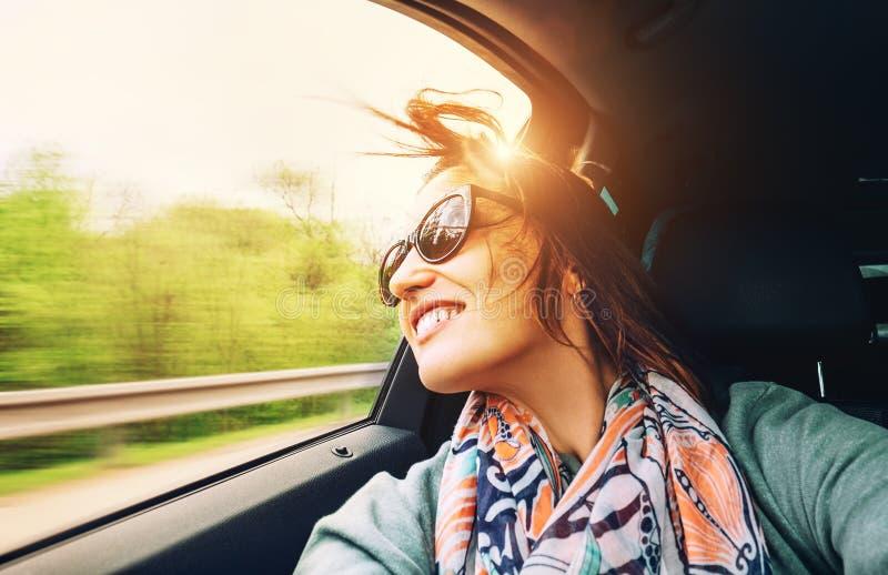 A mulher sente livre e olha para fora do carro da janela aberta imagem de stock
