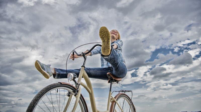 A mulher sente livre quando aprecie dar um ciclo A menina monta o fundo do c?u da bicicleta O ciclismo d?-lhe o sentimento da lib foto de stock