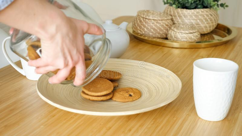 A mulher serve o café da manhã com os biscoitos na tabela na cozinha fotografia de stock