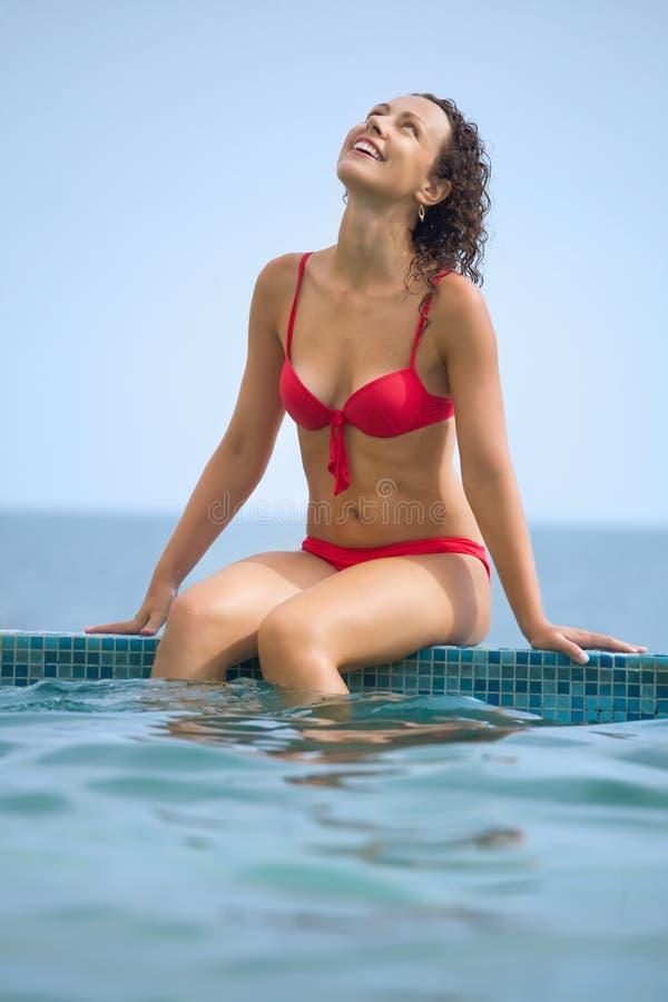 Mulher sexual bonita nova que senta-se na associação da borda imagens de stock royalty free
