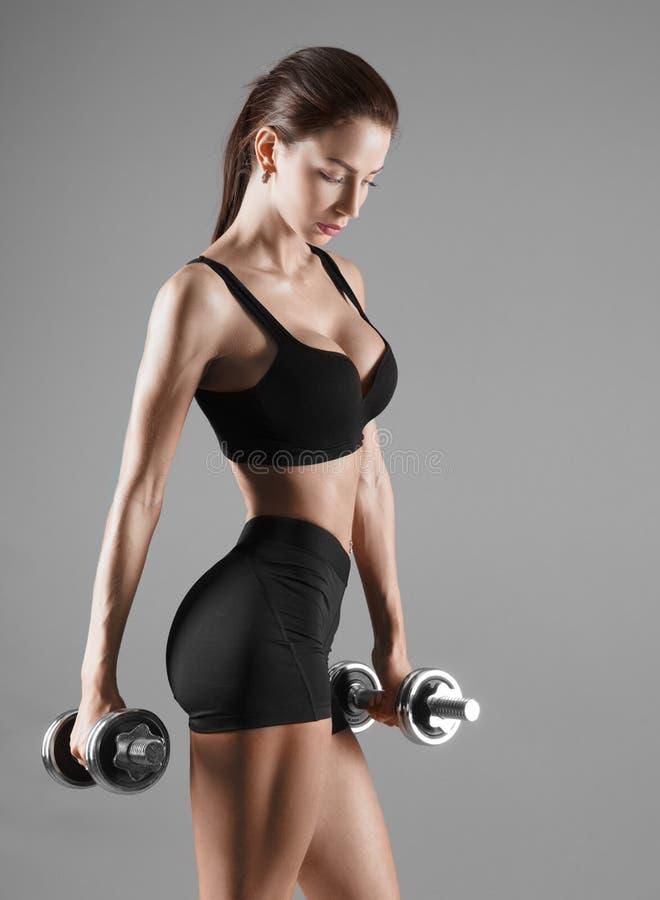 Mulher 'sexy' agradável que faz o exercício com pesos foto de stock