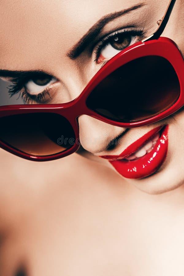 Mulher 'sexy' atrativa em óculos de sol vermelhos foto de stock royalty free