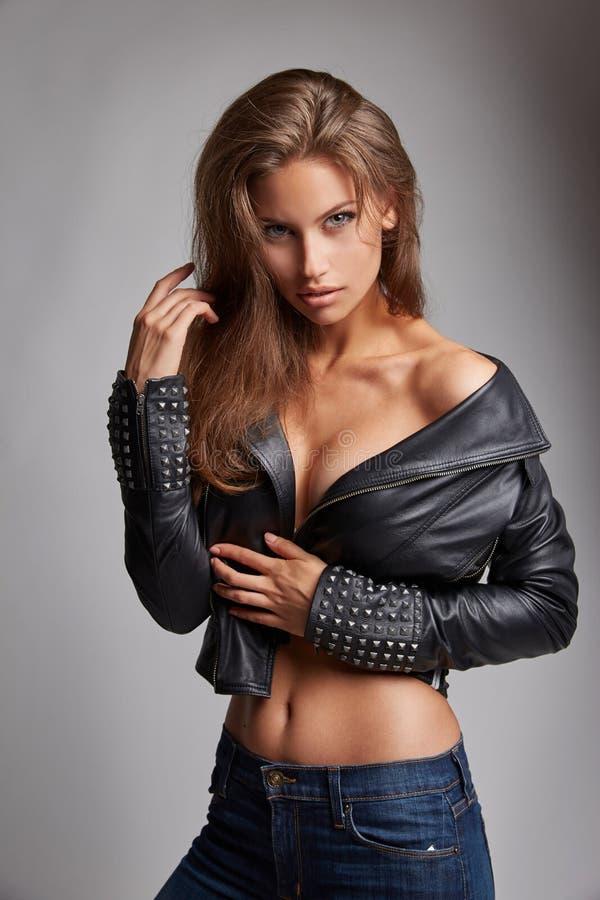 Mulher 'sexy' bonita com cabelo surpreendente e os olhos magníficos no revestimento e na calças de ganga pretos de couro fotografia de stock royalty free