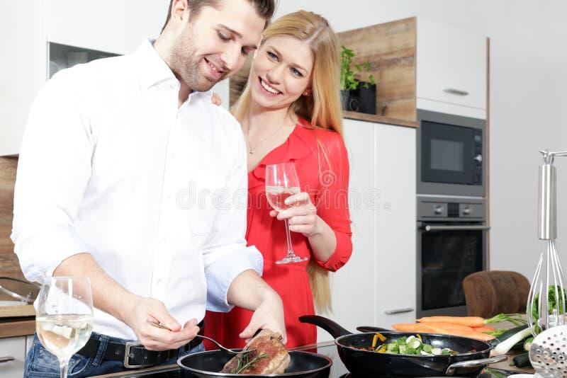 A mulher 'sexy' bonita em um par vermelho do homem do vestido como um cozinheiro está cozinhando em uma cozinha imagens de stock
