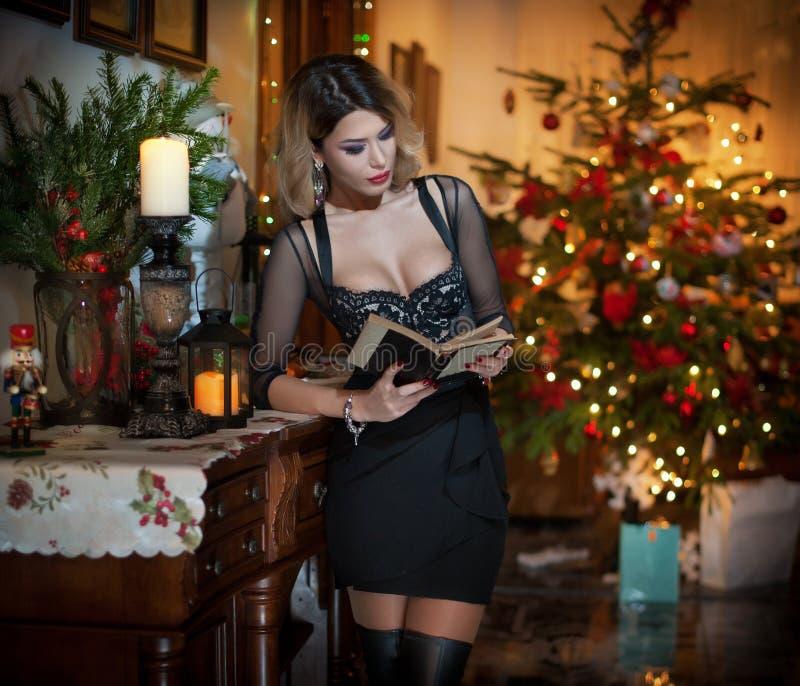 Mulher 'sexy' bonita no vestido preto elegante com a árvore do Xmas no fundo Retrato da menina loura elegante que guarda um livro fotos de stock