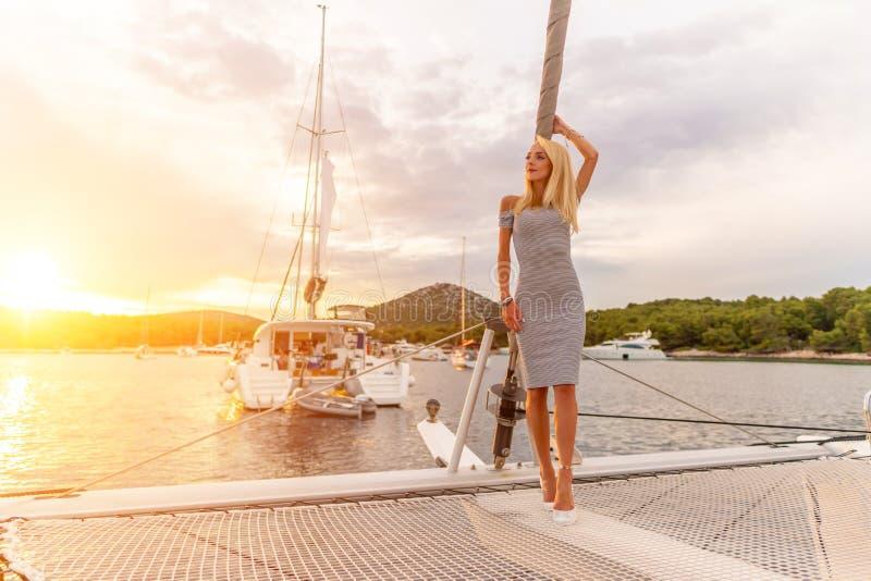 Mulher 'sexy' bonita no vestido que relaxa em uma parte dianteira do iate no por do sol foto de stock