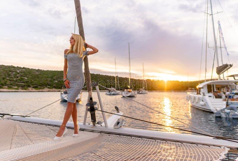 Mulher 'sexy' bonita no vestido que relaxa em uma parte dianteira do iate no por do sol fotografia de stock