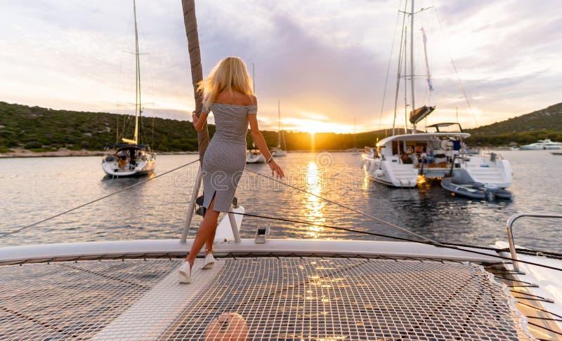 Mulher 'sexy' bonita no vestido que relaxa em uma parte dianteira do iate no por do sol fotos de stock