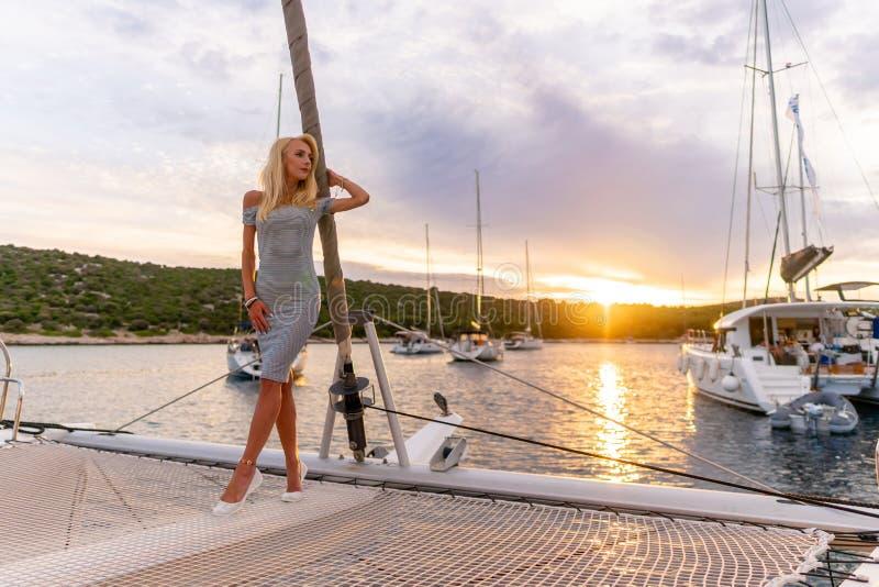 Mulher 'sexy' bonita no vestido que relaxa em uma parte dianteira do iate no por do sol imagens de stock royalty free