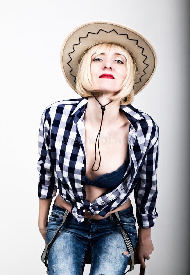 Mulher 'sexy' bonita nova em calças de brim de uma camisa de manta e em um chapéu de vaqueiro fotos de stock royalty free
