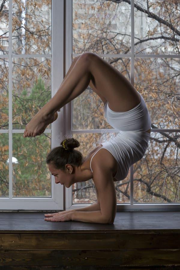 Mulher 'sexy' bonita nova que faz a ioga na janela foto de stock