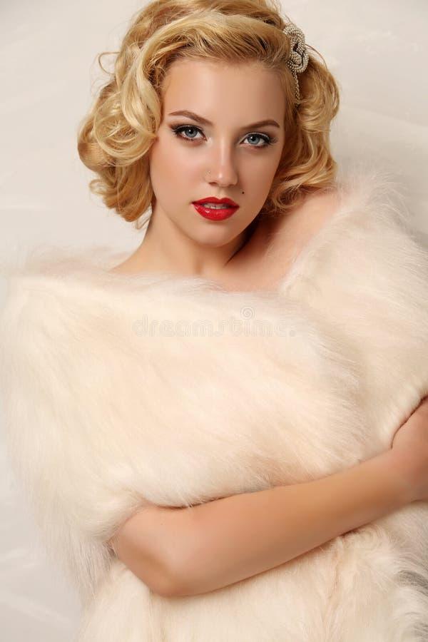 A mulher 'sexy' com cabelo encaracolado louro e composição brilhante, veste a pele imagem de stock royalty free