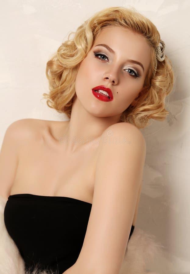 A mulher 'sexy' com cabelo encaracolado louro e composição brilhante, veste a pele foto de stock