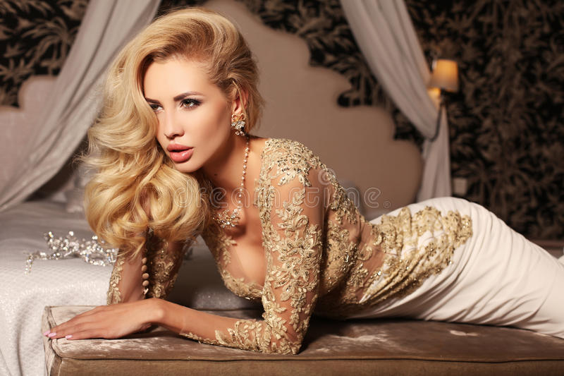 A mulher 'sexy' com cabelo louro longo veste o vestido de casamento do laço dos luxurios e a joia imagem de stock royalty free