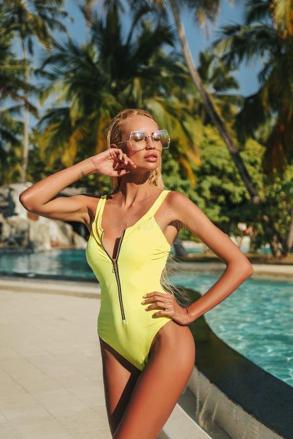 Mulher 'sexy' com cabelo louro no nea de relaxamento elegante do terno de natação imagens de stock royalty free