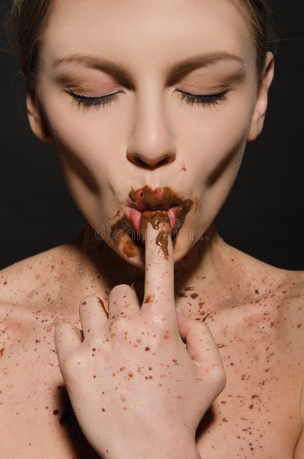 Mulher 'sexy' com chocolate, dedo em sua boca foto de stock