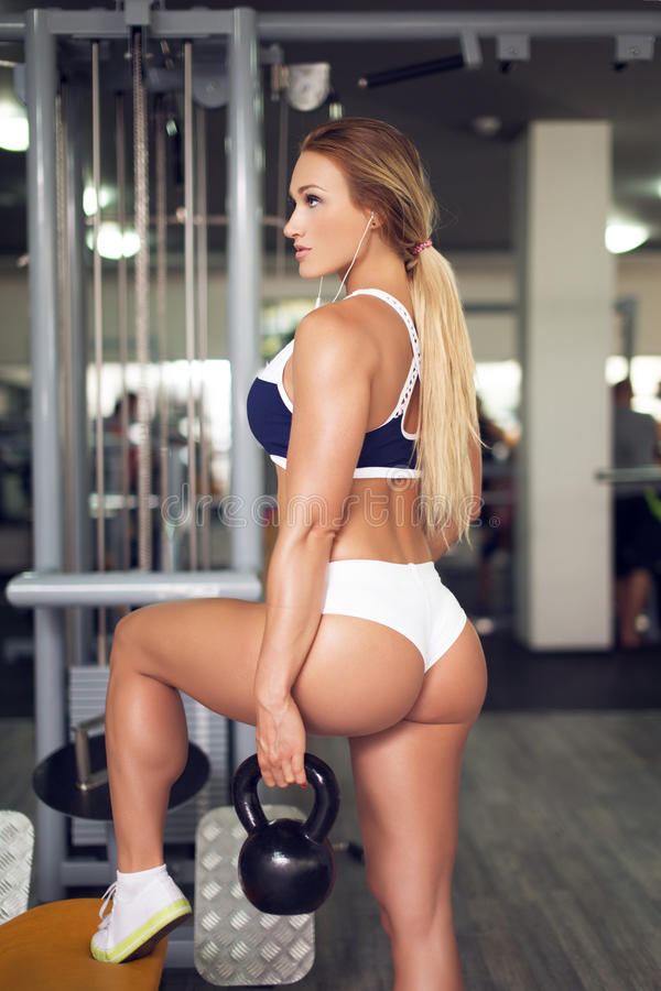 Mulher 'sexy' com exercício do kettlebell no gym imagens de stock royalty free