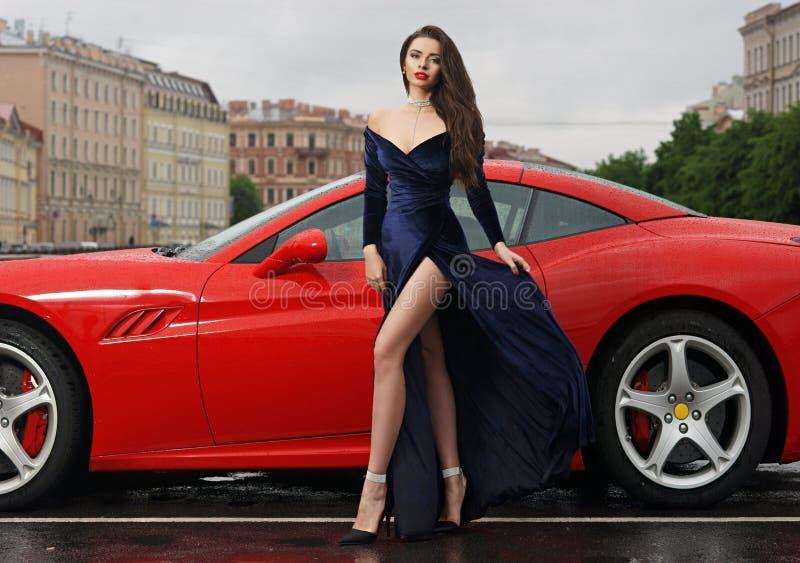 Mulher 'sexy' contra o carro desportivo vermelho imagem de stock