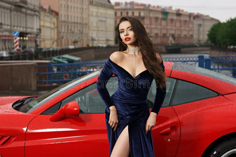 Mulher 'sexy' contra o carro desportivo vermelho imagem de stock royalty free