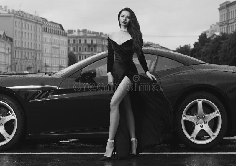 Mulher 'sexy' contra o carro desportivo vermelho fotografia de stock royalty free