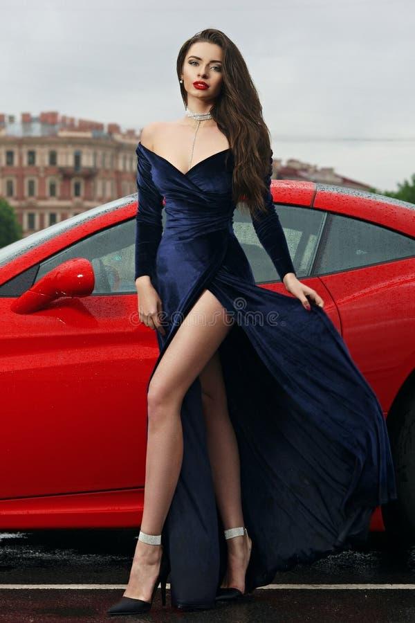 Mulher 'sexy' contra o carro desportivo vermelho imagens de stock