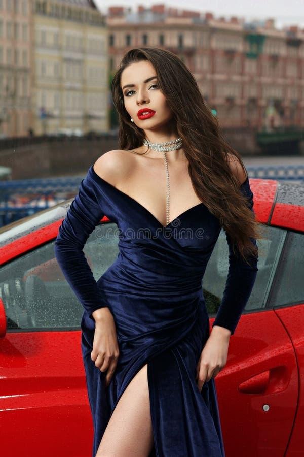 Mulher 'sexy' contra o carro desportivo vermelho foto de stock