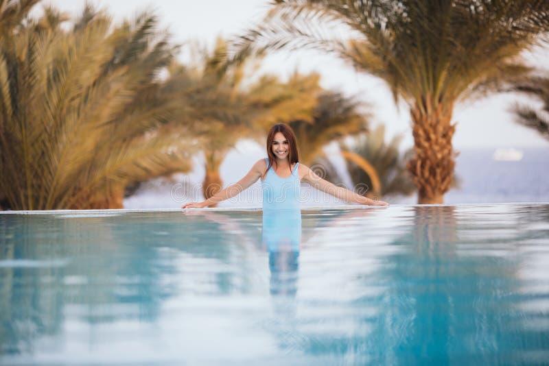 A mulher 'sexy' da beleza no roupa de banho que levanta e relaxa na piscina com palmas e no mar no fundo no recurso luxuoso Voca  fotografia de stock