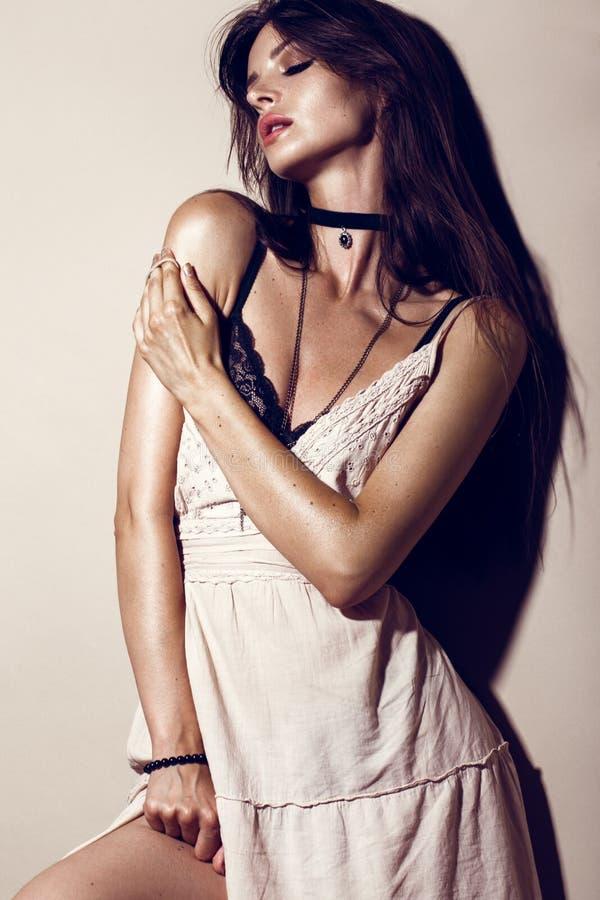 Mulher 'sexy' da forma do encanto com pele bronzeada, cabelo fraco, nivelando a composição em um vestido do verão e em um roupa i foto de stock