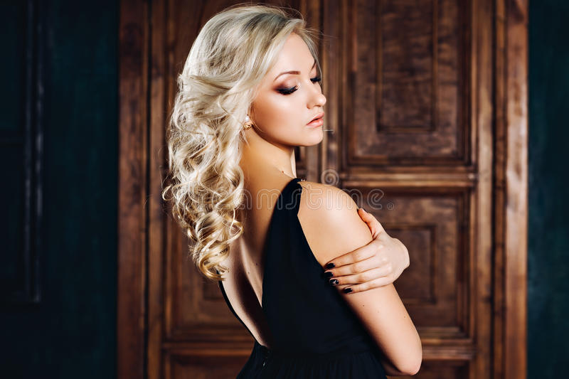 Mulher 'sexy' de fascínio no vestido de noite no interior luxuoso Menina delgada rica à moda com penteado e composição brilhante imagens de stock
