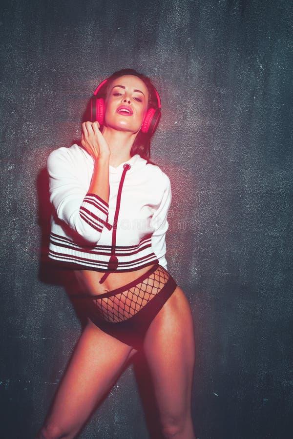 Mulher 'sexy' do DJ com os fones de ouvido e a luz vermelha que levantam na parede no clube noturno fotos de stock