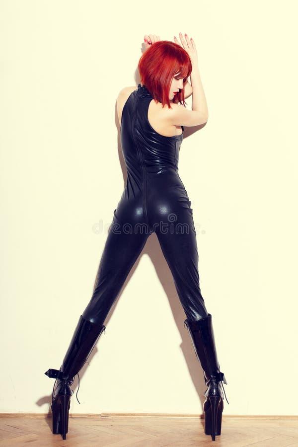 Mulher 'sexy' do dominatrix do ruivo no catsuit do látex que levanta na parede fotografia de stock royalty free