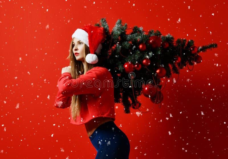 Mulher 'sexy' do esporte da aptidão do Natal que veste o chapéu de Santa que guarda a árvore do xmas em seus ombros Flocos de nev imagens de stock