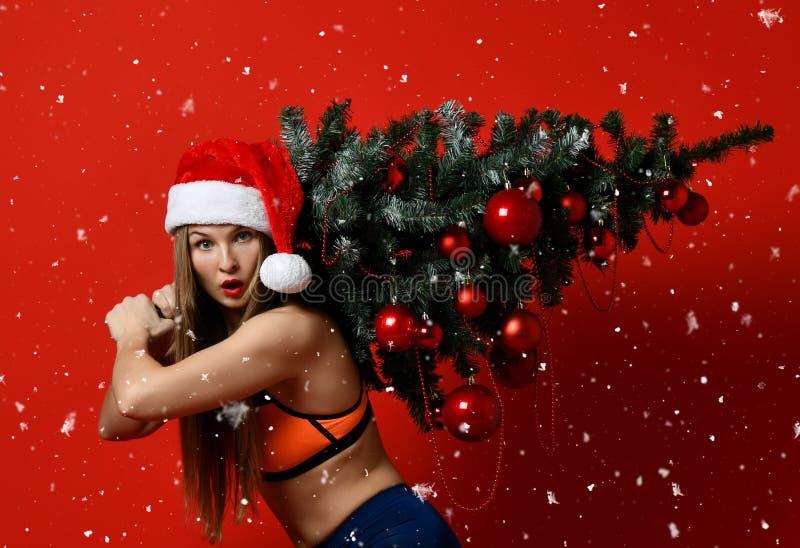 Mulher 'sexy' do esporte da aptidão do Natal que veste o chapéu de Santa que guarda a árvore do xmas em seus ombros Flocos de nev imagens de stock royalty free