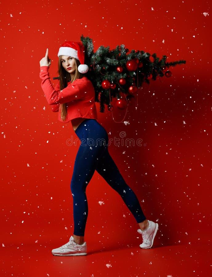 Mulher 'sexy' do esporte da aptidão do Natal que veste o chapéu de Santa que guarda a árvore do xmas em seus ombros Flocos de nev foto de stock