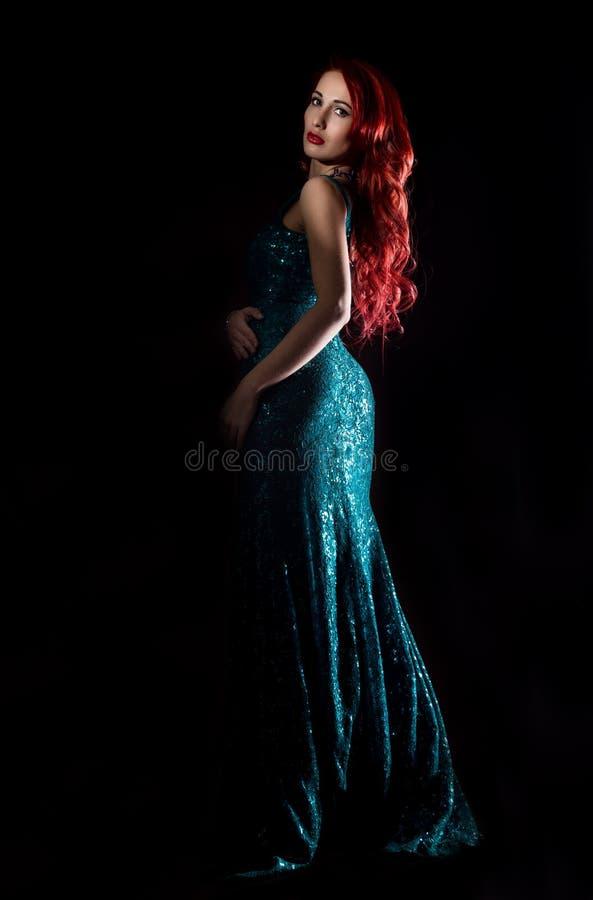 A mulher 'sexy' do ruivo novo no vestido elegante azul levanta em uma obscuridade imagens de stock