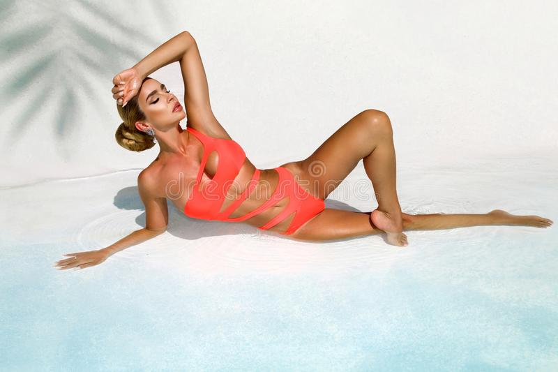 A mulher 'sexy' elegante no biquini alaranjado no corpo magro e escultural sol-bronzeado est? levantando perto da piscina - image imagens de stock