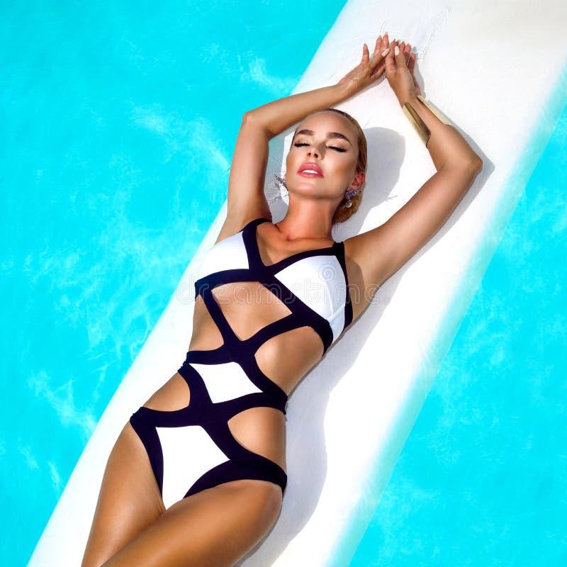 A mulher 'sexy' elegante no biquini preto e branco no corpo magro e escultural sol-bronzeado está levantando perto da piscina - i fotografia de stock