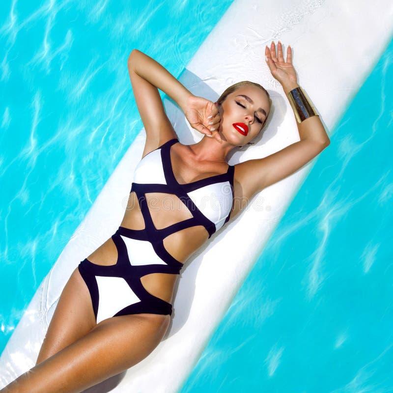 A mulher 'sexy' elegante no biquini preto e branco no corpo magro e escultural sol-bronzeado está levantando perto da piscina - i foto de stock royalty free