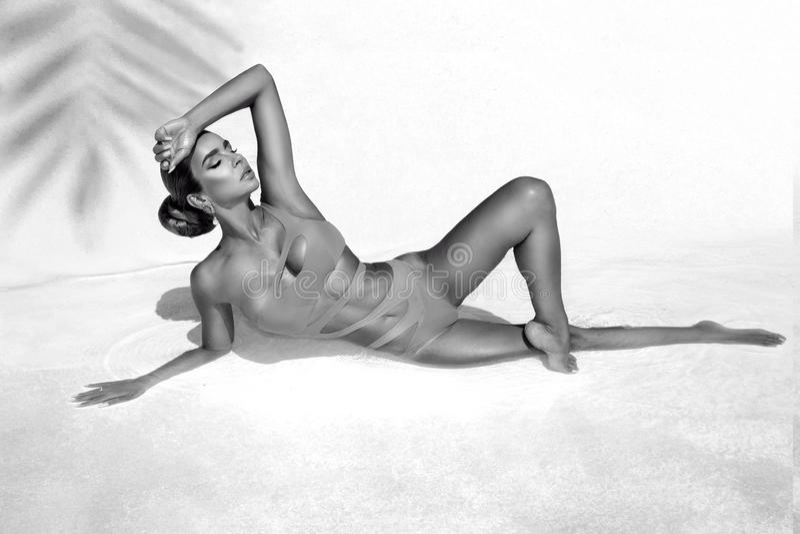 A mulher 'sexy' elegante no biquini surpreendente no corpo magro e escultural sol-bronzeado está levantando perto da piscina Rebe fotografia de stock