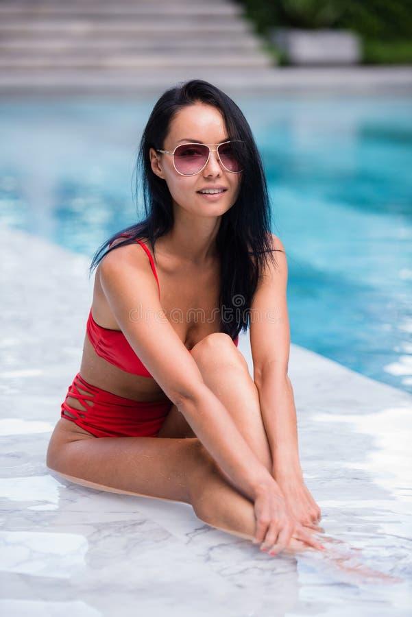 A mulher 'sexy' elegante no biquini vermelho no corpo magro e escultural sol-bronzeado está levantando perto da piscina fotografia de stock royalty free