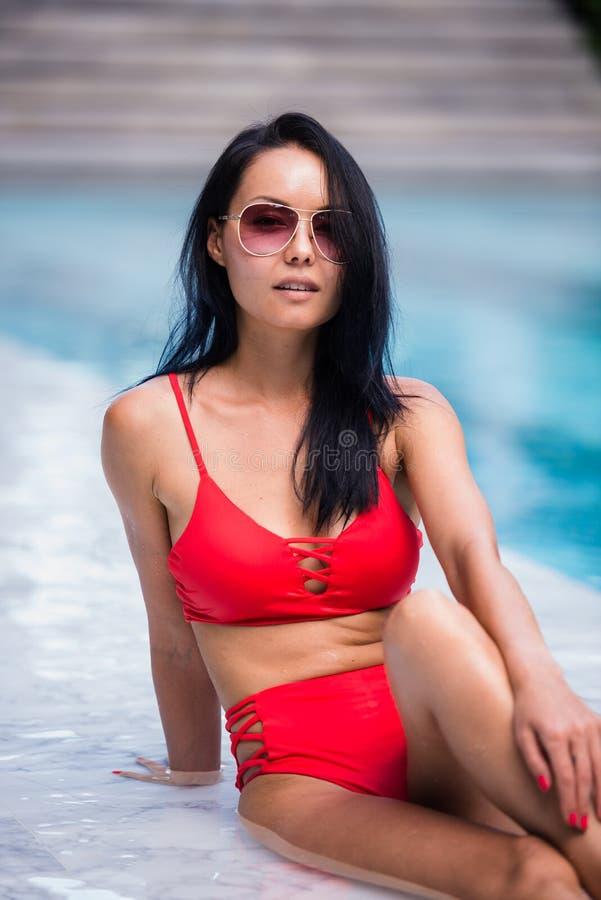 A mulher 'sexy' elegante no biquini vermelho no corpo magro e escultural sol-bronzeado está levantando perto da piscina fotos de stock royalty free