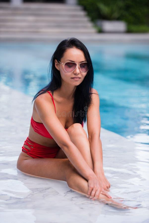 A mulher 'sexy' elegante no biquini vermelho no corpo magro e escultural sol-bronzeado está levantando perto da piscina foto de stock royalty free