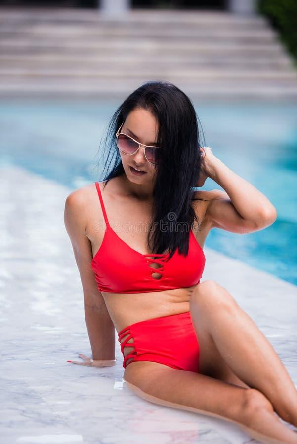 A mulher 'sexy' elegante no biquini vermelho no corpo magro e escultural sol-bronzeado está levantando perto da piscina imagens de stock royalty free