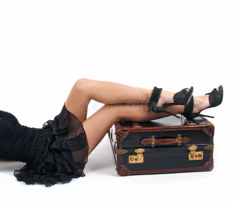 Mulher 'sexy' em pouco vestido preto que mantém os pés em uma mala de viagem do vintage imagem de stock