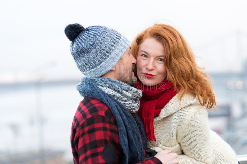 A mulher 'sexy' escuta homens Mulher feliz da história masculina O homem sussurra à mulher vermelha do cabelo Feche acima dos par fotografia de stock