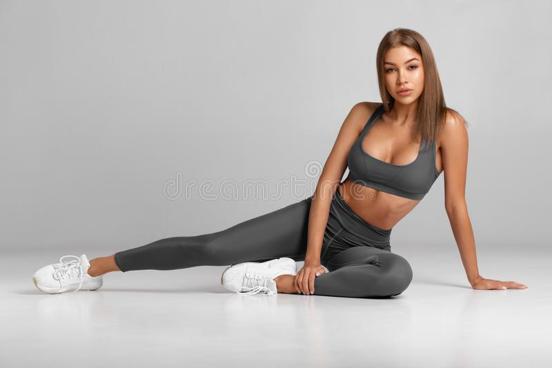 Mulher sexy fitness Linda menina atlética, isolada no fundo cinza foto de stock royalty free