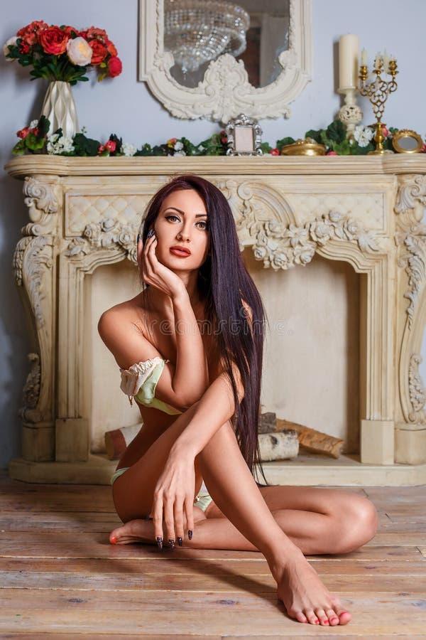 Mulher 'sexy' moreno bonita que senta-se em seu roupa interior no assoalho fotografia de stock