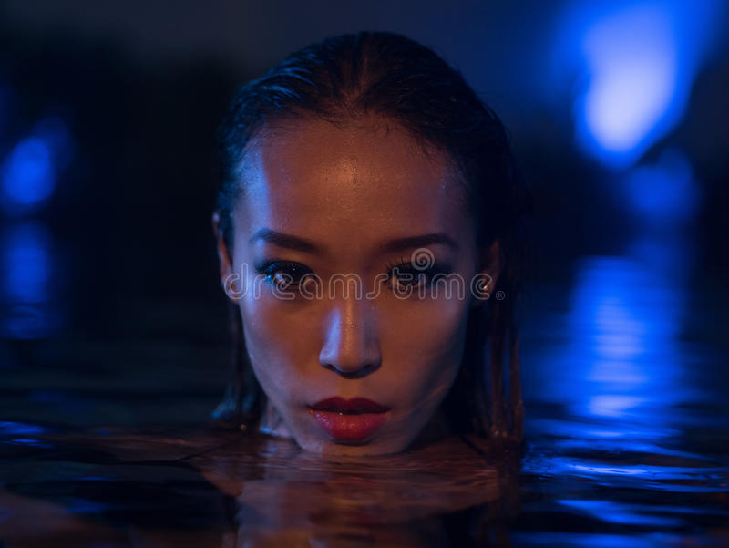 Mulher 'sexy' na piscina no tempo da noite fotos de stock