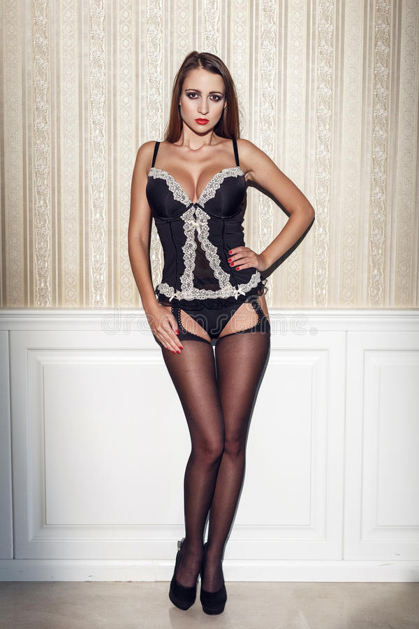 Mulher 'sexy' na roupa interior que está na parede imagens de stock