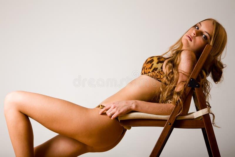 Mulher 'sexy' na roupa interior que levanta na cadeira de dobradura fotografia de stock royalty free
